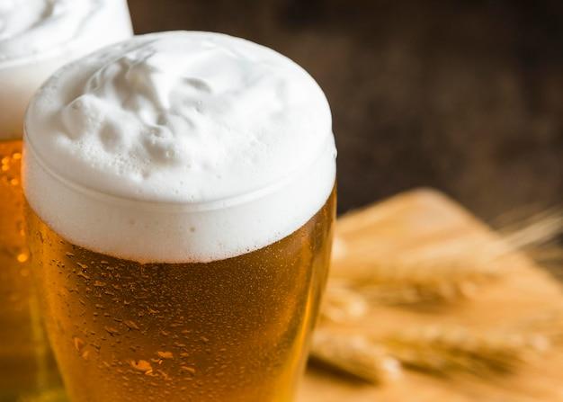 Alto ángulo de vasos de cerveza con espuma