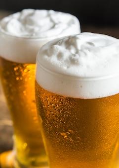 Alto ángulo de vasos de cerveza con mucha espuma