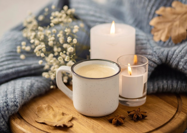 Alto ángulo de velas encendidas con taza de café y suéter