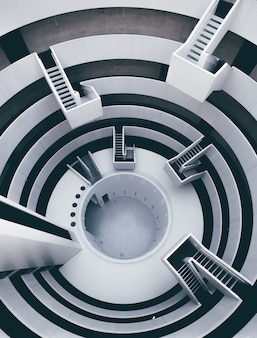 Alto ángulo vertical de un interior en blanco y negro con muchas escaleras