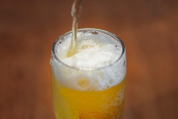 Alto ángulo vertiendo cerveza en medio litro sobre la mesa