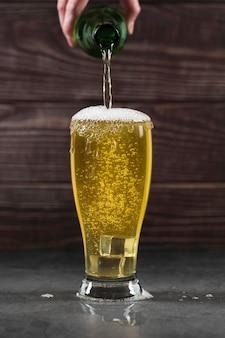 Alto ángulo vertiendo cerveza en vaso