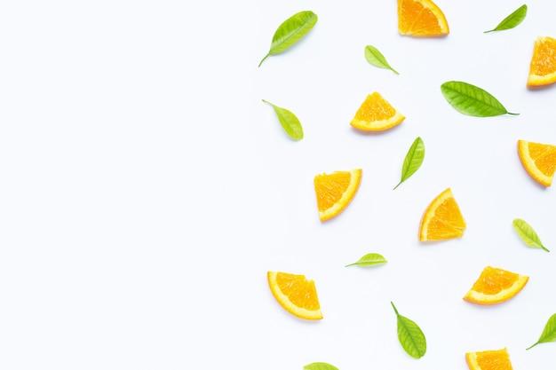 Alto contenido de vitamina c, jugosa y dulce. fruta fresca de naranja con hojas verdes sobre fondo blanco con copyspace