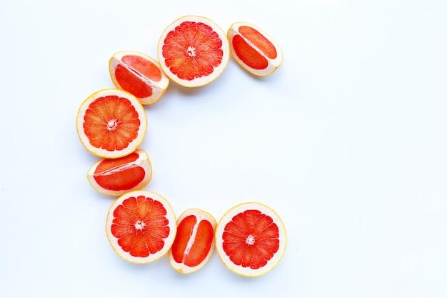 Alto contenido de vitamina c, letra c hecha de rodajas de pomelo aisladas sobre fondo blanco.