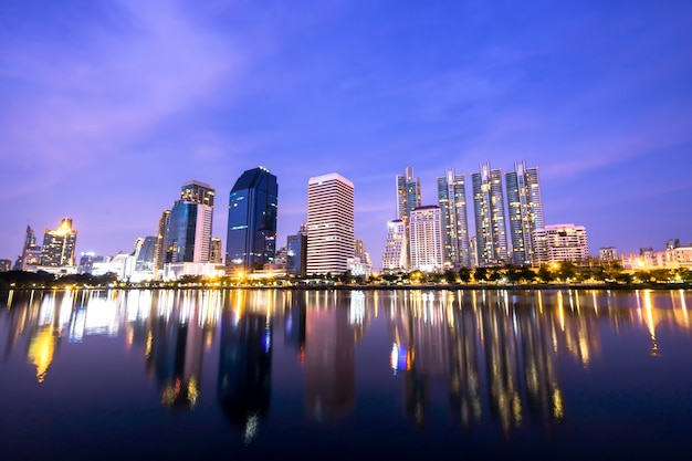 Los altos edificios reflejan el lago en la noche en bangkok, tailandia.