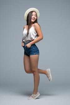 Altura completa chica asiática en sombrero de paja sobre fondo gris