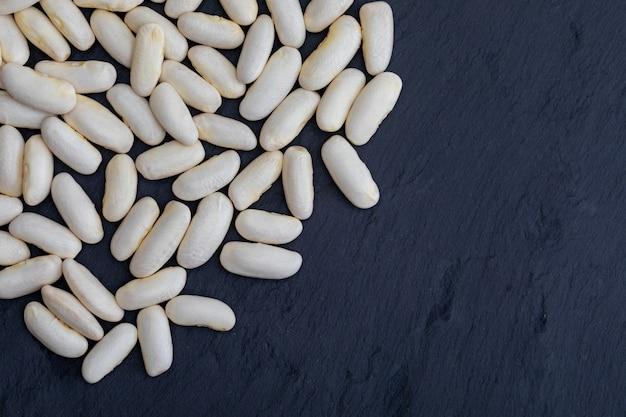 Alubias blancas (fabes) crudas (legumbres) sobre fondo de pizarra negra con textura. con espacio para insertar tu texto aquí.