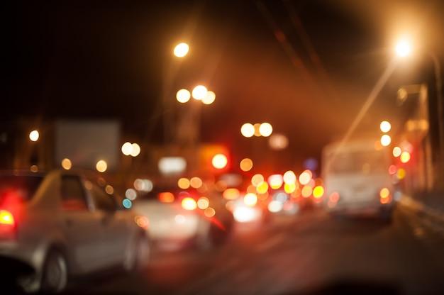Alumbrado nocturno de la ciudad faroles y coches.