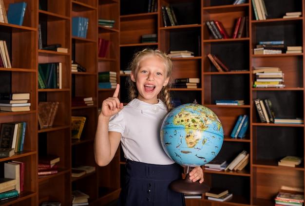 Una alumna feliz apunta su dedo hacia arriba y sostiene un globo terráqueo en la escuela