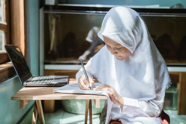 Alumna de indonesia estudiando la tarea durante su lección en línea en casa