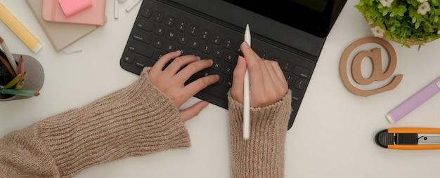 Alumna manos usando tableta digital con teclado y lápiz óptico sobre mesa blanca con papelería