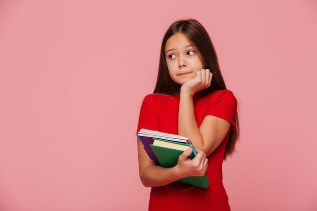 Alumna pensativa sosteniendo libros y mirando a un lado sobre rosa