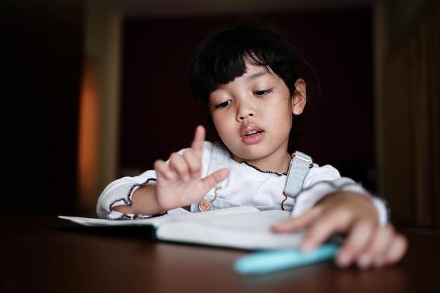 La alumna resuelve la tabla de multiplicar en su cuaderno y cuenta con los dedos.
