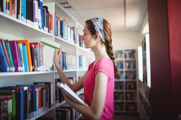 Alumna seleccionando el libro del estante de libros en la biblioteca