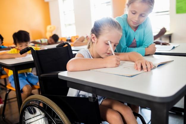 Alumno ayudando a otro en el escritorio