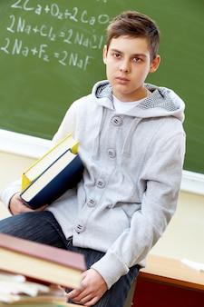 Alumno en clase con la pizarra de fondo