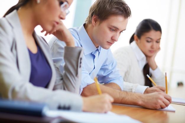 Alumno concentrado escribiendo su idea