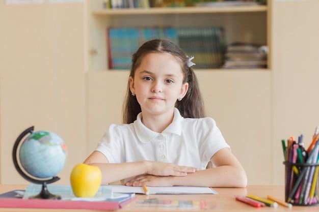 Alumno diligente sentado en el escritorio