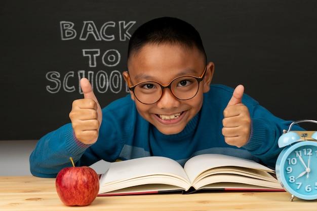 Alumno de la escuela primaria en unas gafas con la mano levantada. el niño está listo para aprender. de vuelta a la escuela.