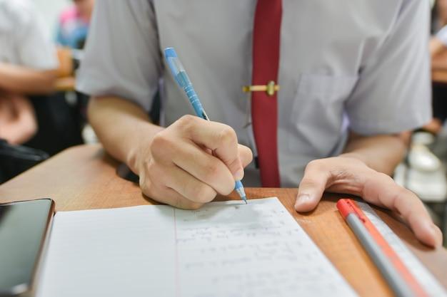 Alumno haciendo tarea o tomando un examen escrito en la universidad