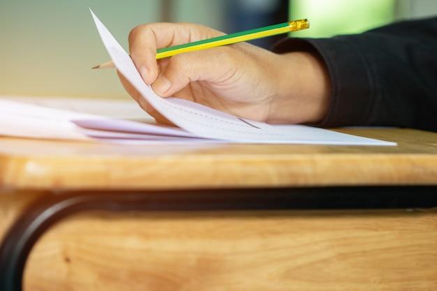 Alumno que toma exámenes, examen de escritura en papel hoja de respuestas forma óptica de prueba estandarizada