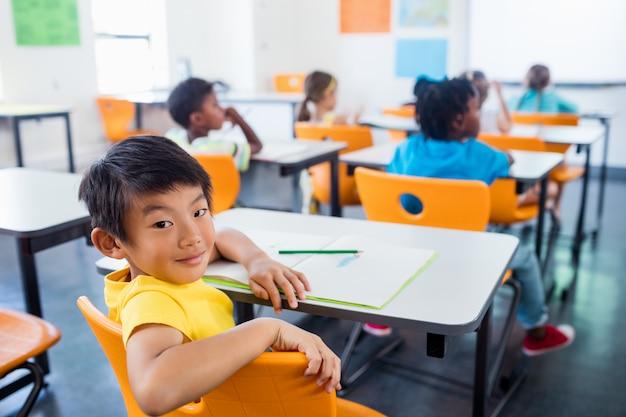 Alumno sentado en su escritorio mirando a la cámara en el aula