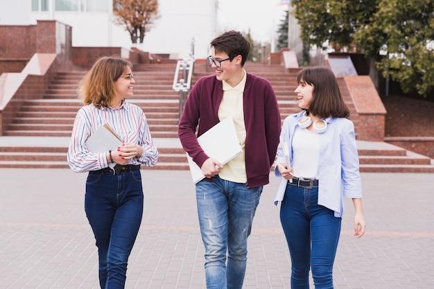 Alumnos adolescentes caminando con libros y hablando de lecciones.