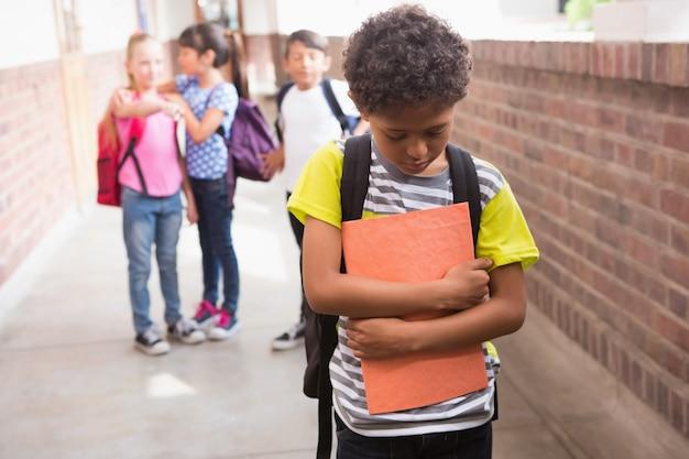 Alumnos amigos burlándose de un alumno solo