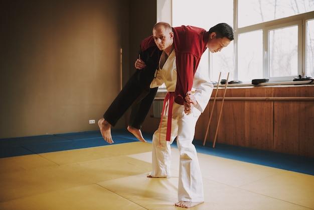 Alumnos de artes marciales en blanco y rojo practicando técnicas.