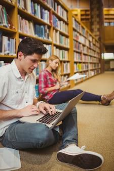 Alumnos concentrados trabajando en el piso de la biblioteca.