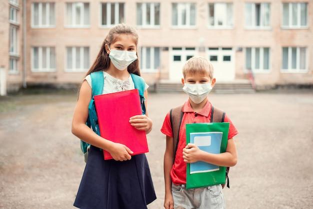 Alumnos escolares de diferentes edades frente a la escuela convencional en máscaras médicas