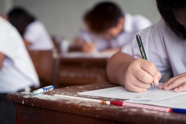Alumnos escribiendo respuesta haciendo un examen en el aula.