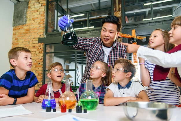 Los alumnos de la escuela primaria observan atentamente a su maestro que muestra interesantes experimentos químicos con líquidos coloreados en láminas de vidrio.