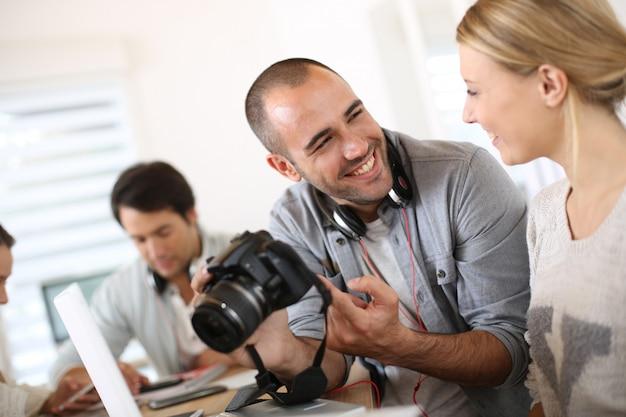Alumnos de fotografía trabajando juntos en proyecto.