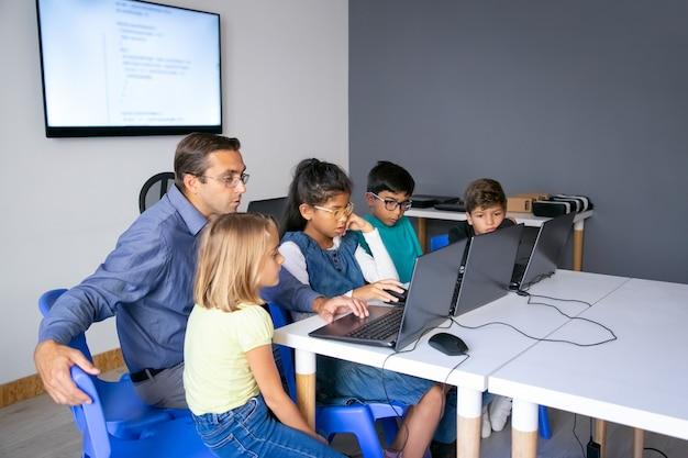 Alumnos multiétnicos haciendo tareas con la ayuda del profesor