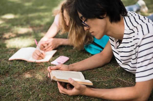 Alumnos multirraciales con libros sobre hierba verde.
