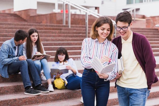 Alumnos de pie juntos con cuaderno abierto.