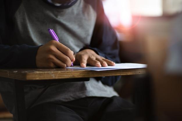 Alumnos que escriben bolígrafo en mano haciendo exámenes contestan ejercicios en el aula con estrés.