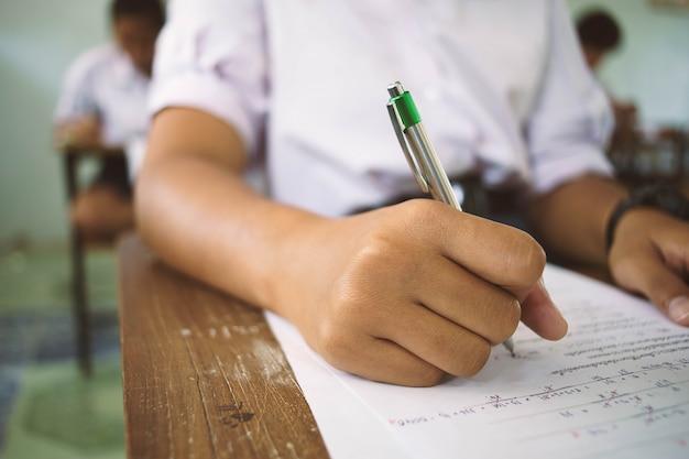 Alumnos que sostienen la pluma en la mano haciendo exámenes contestan hojas ejercicios en el aula con estrés.