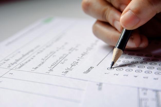 Los alumnos sostienen la escritura de lápiz con la opción seleccionada en las hojas de respuestas y las hojas de preguntas de matemáticas