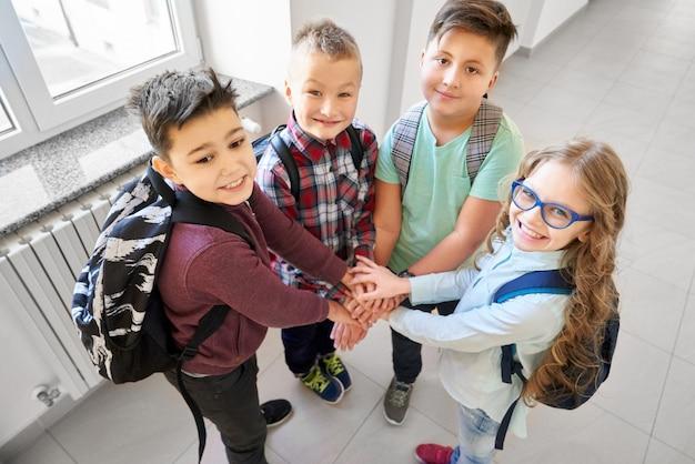 Alumnos tomados de la mano juntos uno debajo del otro.