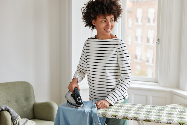 Ama de casa alegre hace las tareas del hogar en casa