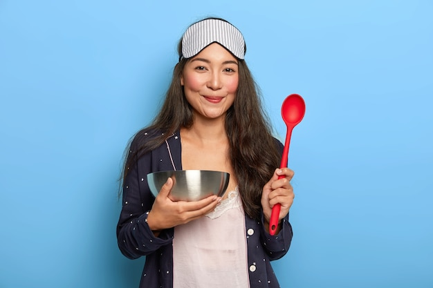 Ama de casa alegre sostiene un cuenco y una cuchara de acero, se despierta temprano en la mañana para preparar un plato sabroso, prueba una nueva receta, tiene una ración saludable, usa pijama