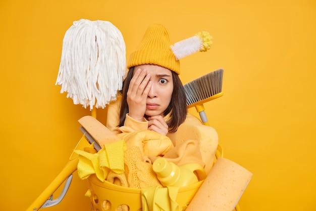 Ama de casa asiática asustada preocupada parece asustada cuando nota que la habitación muy sucia está ocupada con la limpieza rodeada de trapeadores, escoba, cepillo, pila de detergentes químicos para ropa aislados sobre una pared amarilla