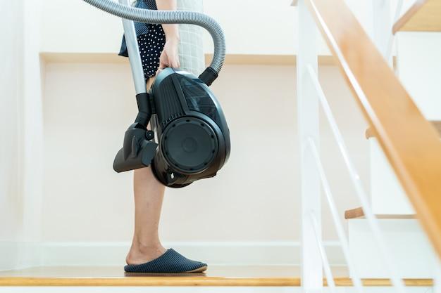 Ama de casa asiática que se coloca en la escalera y que lleva ascendente cercano del vacío.