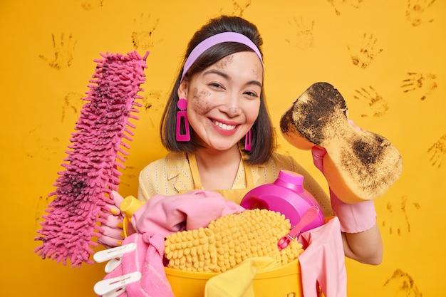 Ama de casa asiática satisfecha usa diadema y aretes tiene la cara sucia después de quitar el polvo posa con una esponja de fregona limpia todo en la casa aislada sobre una pared amarilla