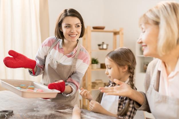 Ama de casa bastante joven con bandeja caliente mostrando a su madre e hija galletas recién horneadas