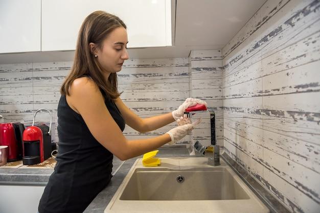 Ama de casa bonita en guantes blancos de limpieza en la cocina con detergente. tareas del hogar