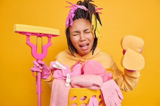 Ama de casa cansada de limpiar la casa todo el día sostiene una esponja y un trapeador expresa emociones negativas vestida con ropa doméstica informal aislada en amarillo