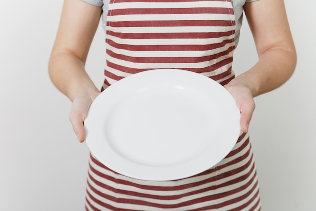 Ama de casa caucásica joven en delantal rayado, camiseta gris aislada. ama de llaves mujer sosteniendo en las manos plato redondo vacío blanco